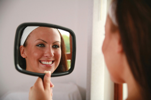 woman smiling in mirror after teeth whitening