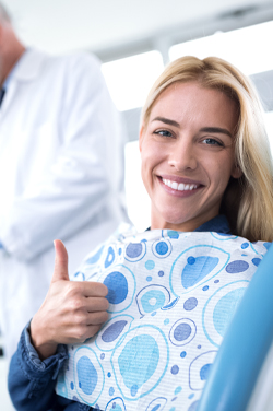 woman in dental chair giving thumbs up